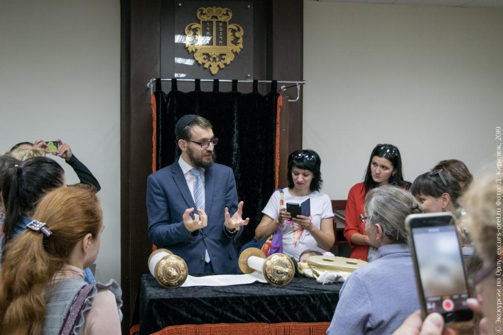 Раввин в синагоге показывает экскурсантам Свиток Торы.