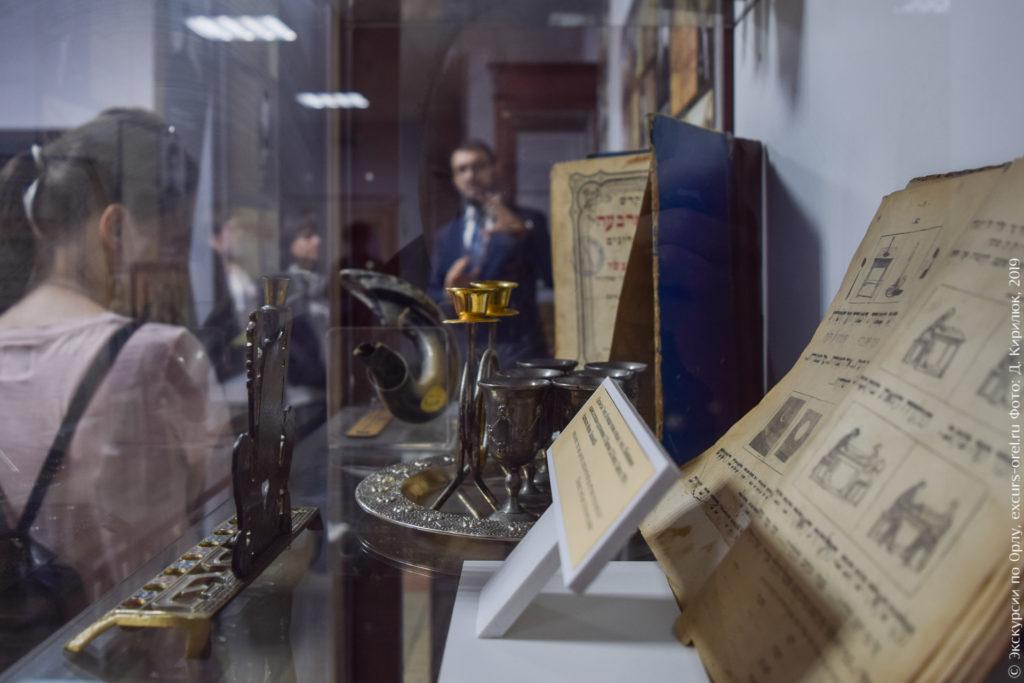 Старые книги на иврите, выделанный рог, металлические ритуальные предметы на фоне раввина и экскурсантов.