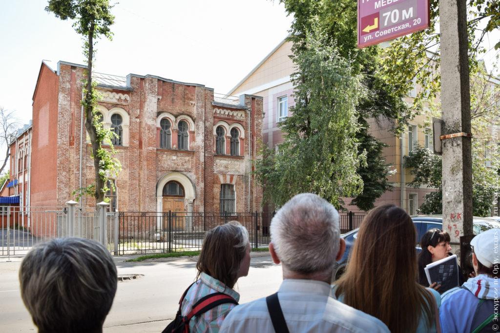 Экскурсанты на фоне двухэтажного красно-белого неоштукатуренного здания в неомавританском стиле.