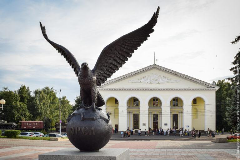 """Памятник в виде орла, распростершего крылья, сидящего на шаре с надписью """"Орел"""". За ним здание в неоклассическом стиле."""