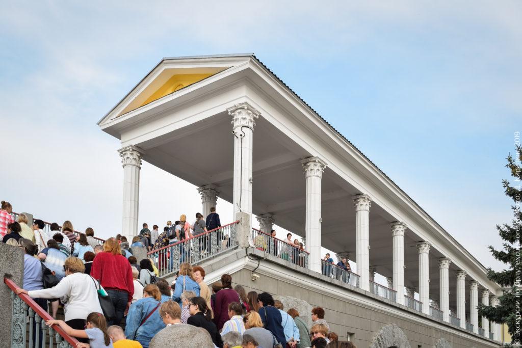 Люди поднимаются по лестнице к колоннаде с треугольным фронтоном.