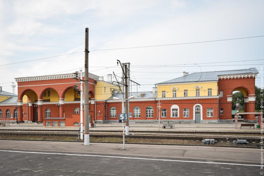 Красно-желтое двухэтажное здание с портиком с широкими арками за железнодорожными путями.