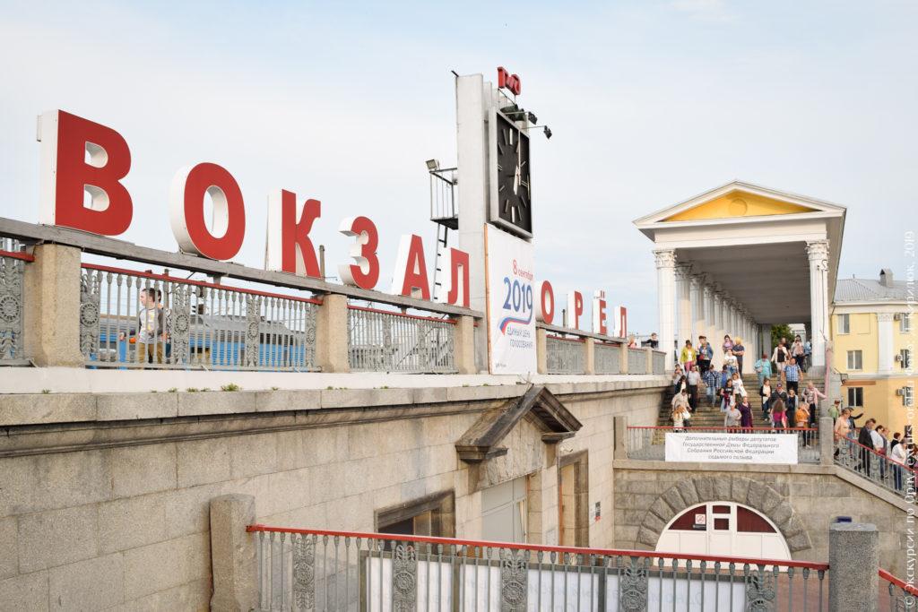 """Квадратные башенные часы между большими словами """"ВОКЗАЛ"""" и """"ОРЁЛ""""."""