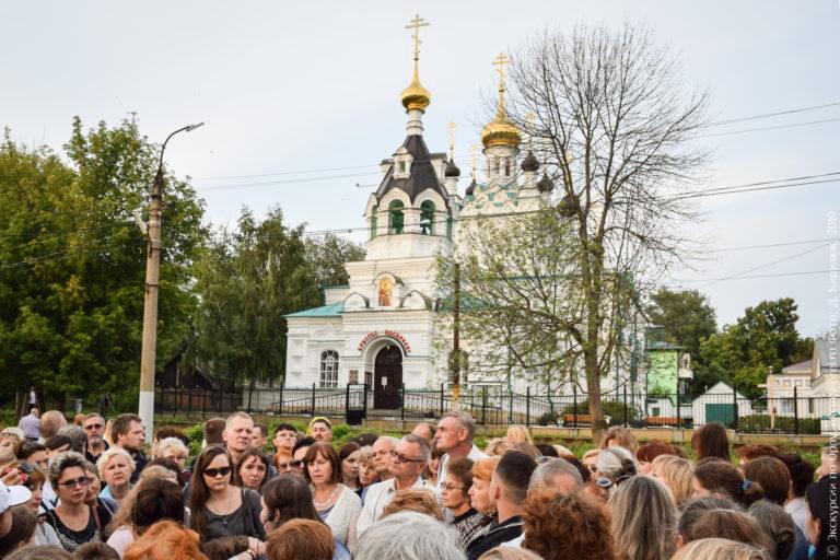 Церковь в неорусском стиле, с шатровой колокольней, белыми стенами и золотыми главками.