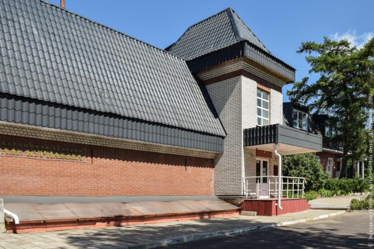 Два кирпичных 2-этажных здания с оранжевыми стенами и черной черепичной крышей.
