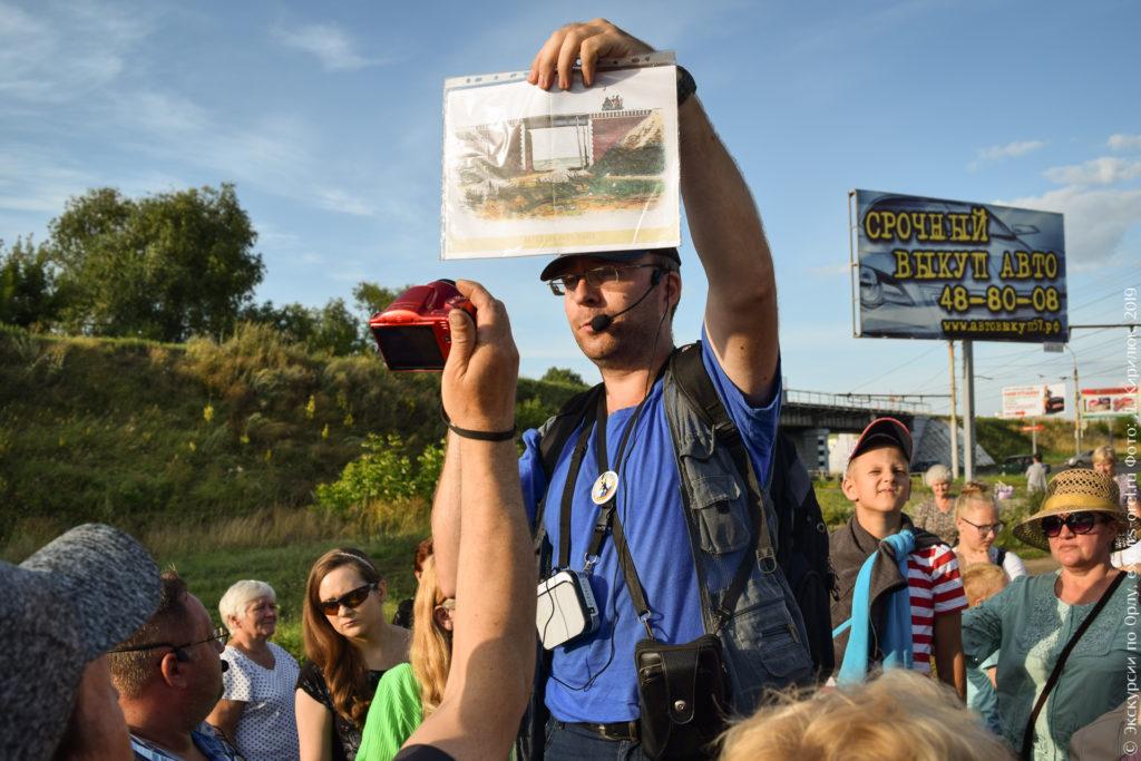 Экскурсовод показывает старое фото путепровода на фоне нынешнего.