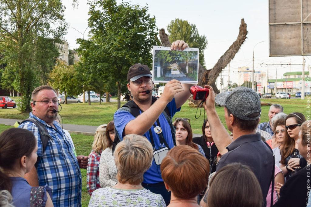 Экскурсовод показывает фото одиночной могилы, окруженной деревьями.