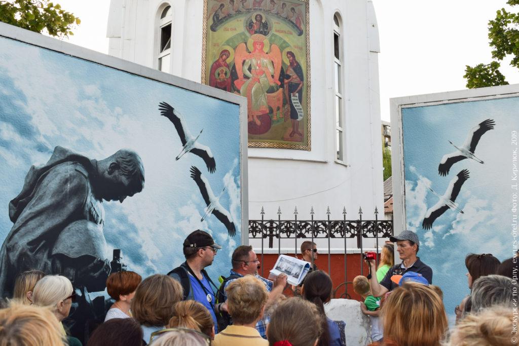 Белая церковь с изображением иконы и стенды с изображением солдата и журавлёв.