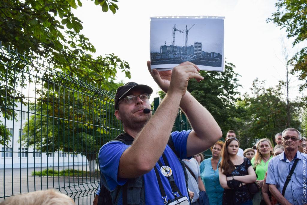 Экскурсовод показывает фото строительной площадки.