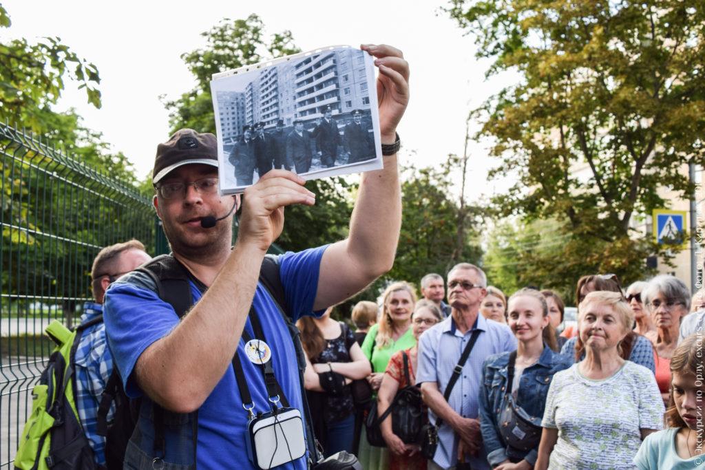 Экскурсовод показывает фото с летчиками на фоне 9-этажного дома.