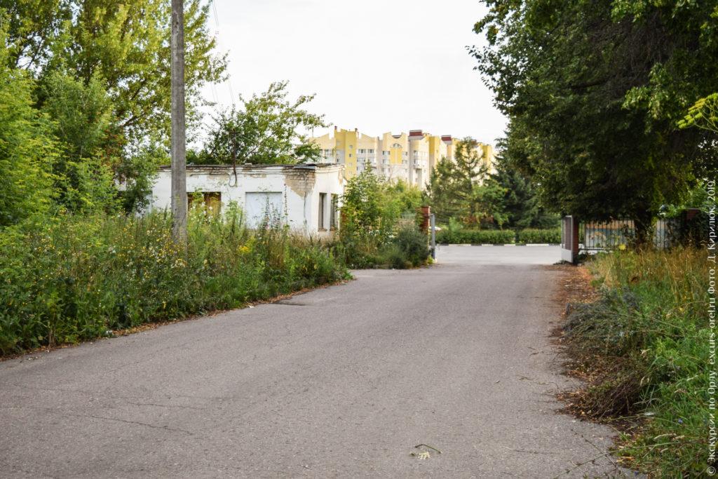 Заросшая с двух сторон асфальтная дорожка, открытые ворота.