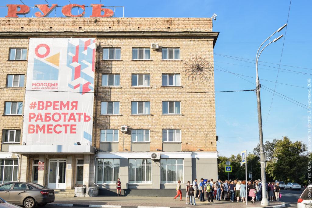 """5-этажное советское здание без архитектурных изысков, на крыше объемная надпись """"РУСЬ"""". На фасаде баннер """"Молодые кадры Орловщины""""."""