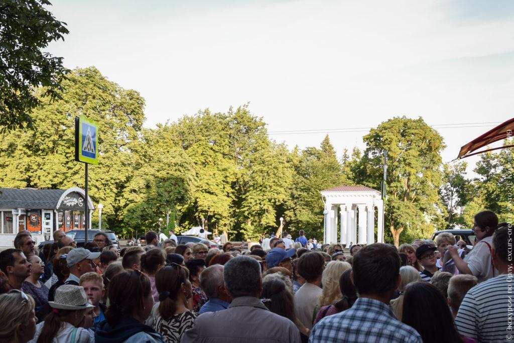 Экскурсанты на фоне парка с колоннадой на входе.