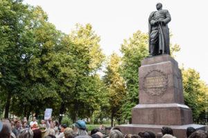 Памятник военному, опирающемуся на саблю, на высоком постаменте.