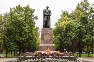 Скульптура генерала, опирающегося на шашку, на высоком гранитном постаменте, на фоне деревьев,