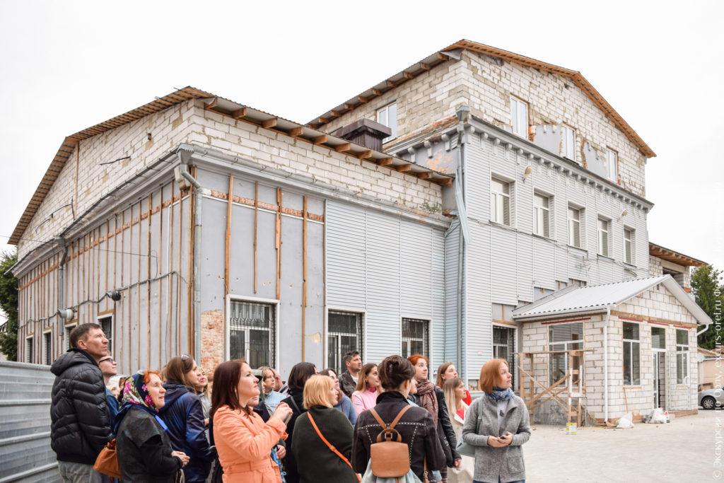 Здание, в котором можно увидеть и старый красный кирпич, и современный силикатный, частично прикрыто серым сайдингом.