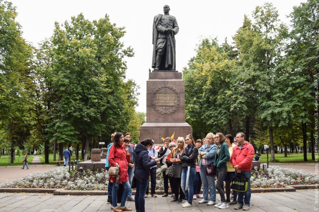 Экскурсанты в сквере на фоне памятника советскому генералу.