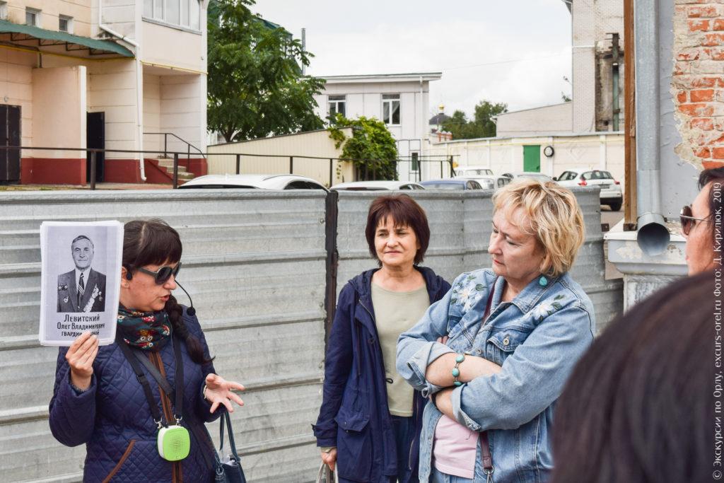 Экскурсовод показывает фото О.В. Левитского.