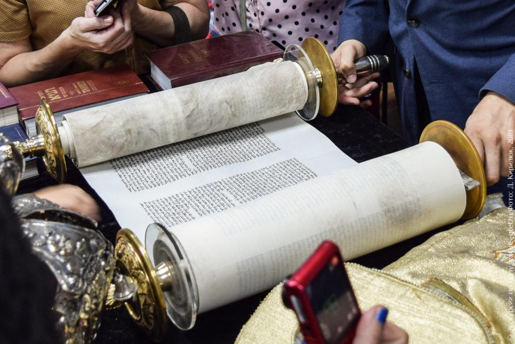 Свиток из пергамента, с убористым каллиграфическим текстом, с рукоятками.