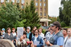 Экскурсовод показывает старую карту, на фоне - деревья и корпус Аграрного университета.
