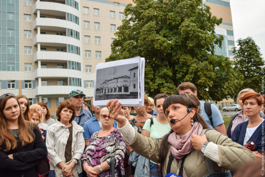 Экскурсовод показывает фото старого 2-этажного корпуса больницы на фоне нового, которое всё не влезает в кадр.