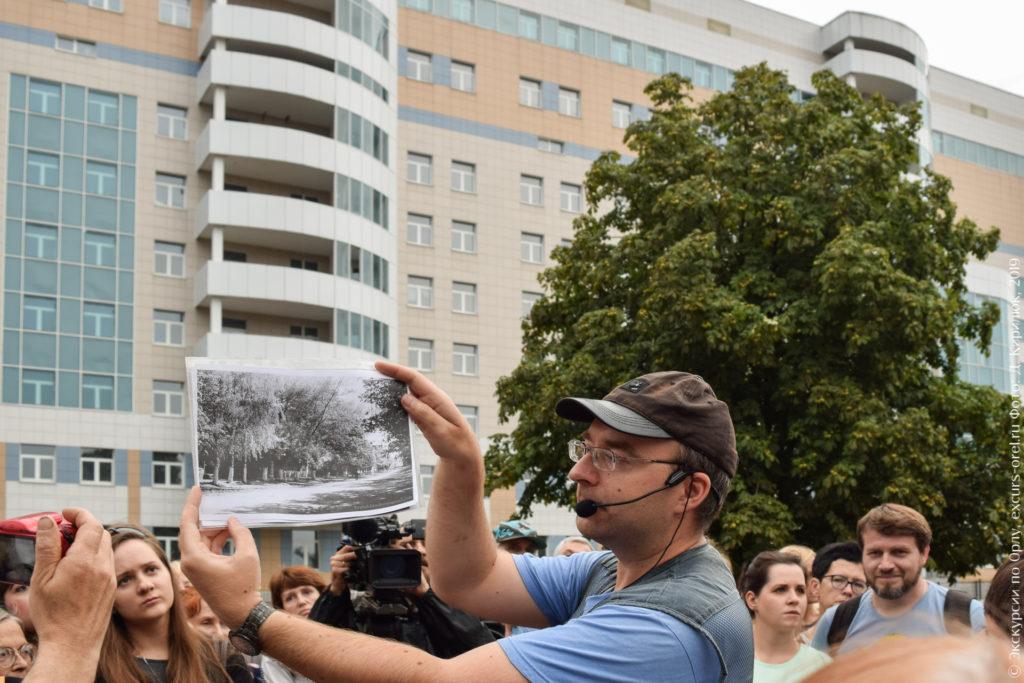 Экскурсовод показывает старое фото, на котором видны в основном деревья.
