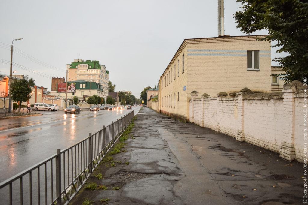 Дождливый серый пейзаж. Вид на уходящую вдаль неприглядную улицу с кривым асфальтом, кирпичным забором и корпусами больницы.