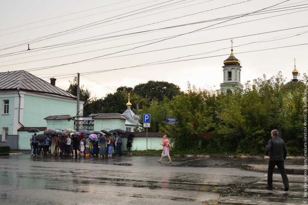 Люди под зонтами у входа на кладбище. Видна зеленая церковь с золотыми главками.