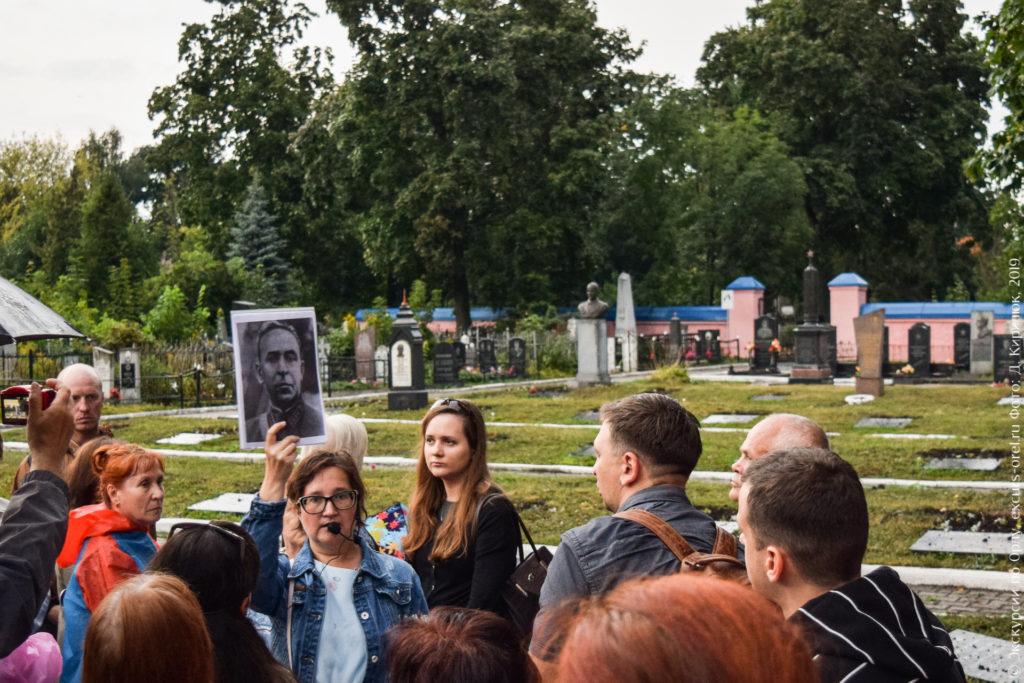 Экскурсанты на фоне военного кладбища с памятниками и плитами в земле.