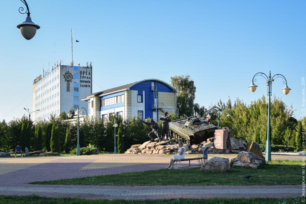 """Сквер с скульптурной композицией с военными и БМП, на заднем плане - высокое здание с изображением на стене орденом и надписью """"Орел город первого салюта""""."""
