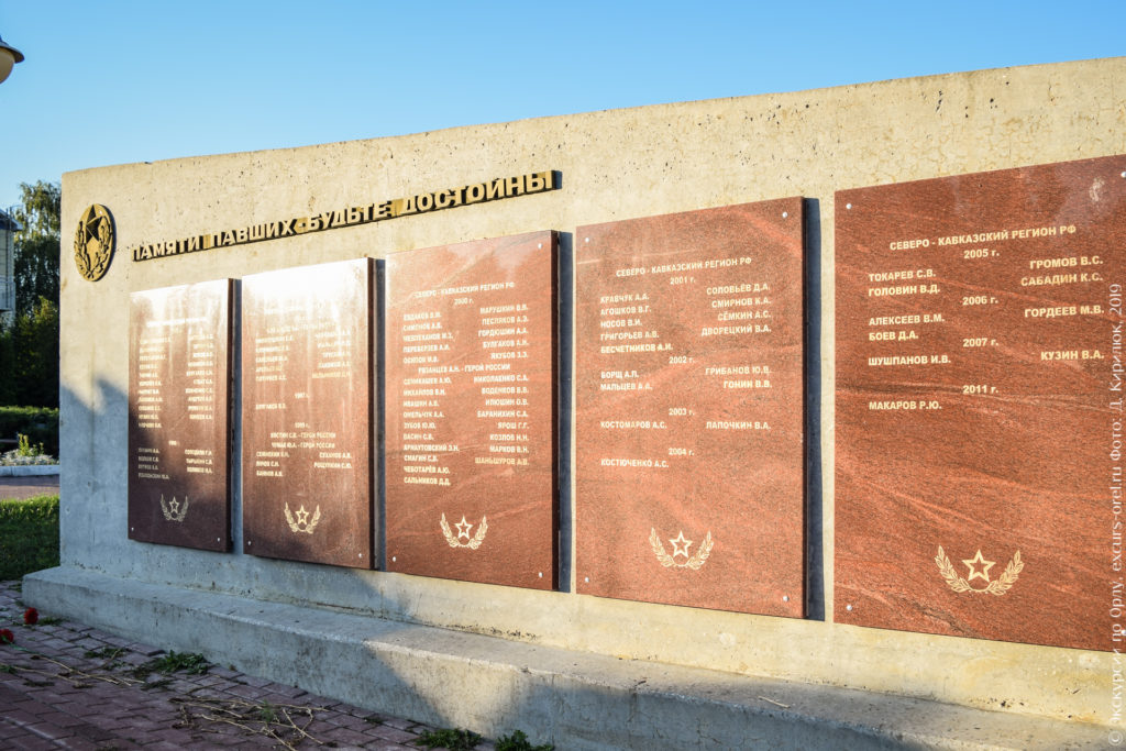 """Серая стена с плитами из красного гранита с именами, датами и названием регионов боевых действий. Надпись над плитами: """"Памяти павших будьте достойны""""."""