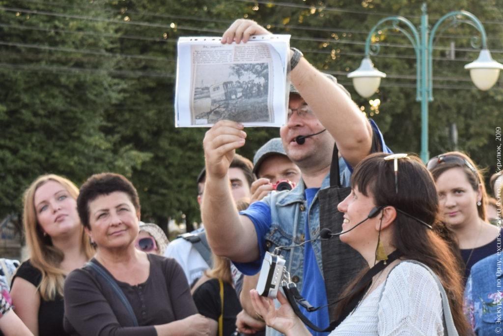 Экскурсовод показывает вырезку из старой газеты с черно-белой фотографией.