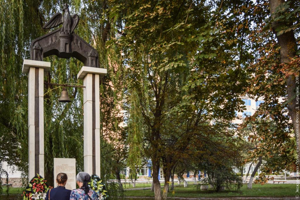 Две прямоугольные белые колонны, увенчанные скульптурным изображением орла на крепости (герб города Орла). На перекладине между колоннами установлен колокол. У основания колонн плита с текстом.