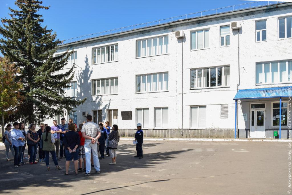 3-этажное белое здание, высокая ель, под ней группа людей.