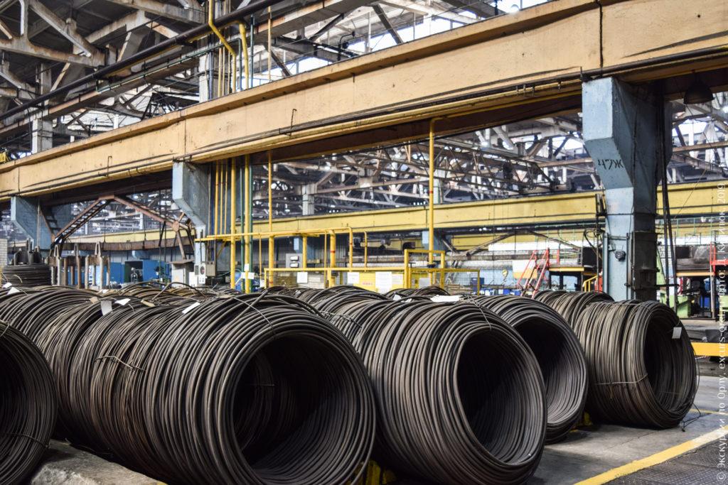 Большие катушки толстой проволоки на заводе.