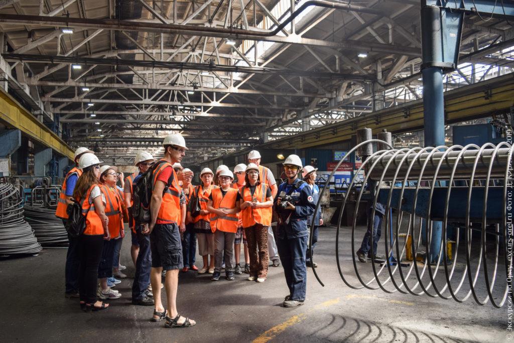 Экскурсанты в оранжевых жилетах изучают заводское оборудование.