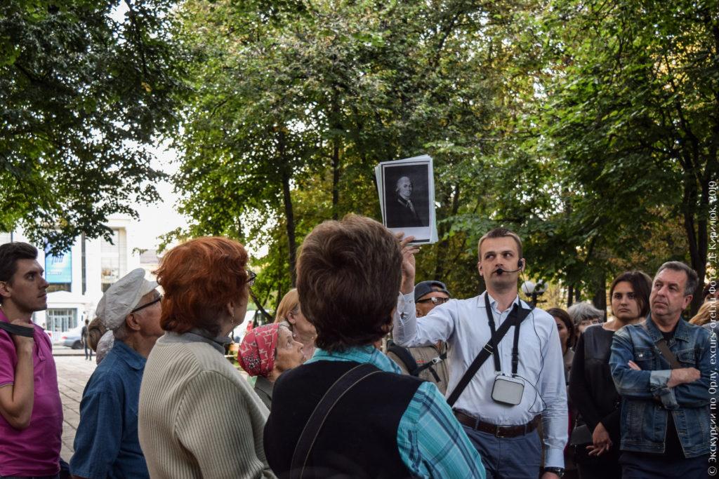 Экскурсовод показывает фото графа С.М. Каменского, сзади - деревья и современное здание в просвете.