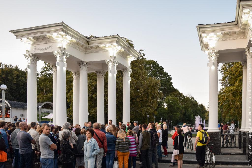 """Люди у недавно отремонтированной колоннады в стиле """"сталинский ампир"""" на входе в городской парк, в глубине виден фонтан с подсветкой."""