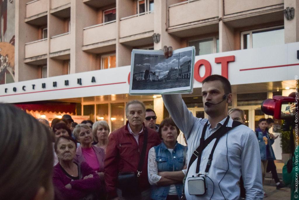 Экскурсовод показывает старое фото Городской думы.