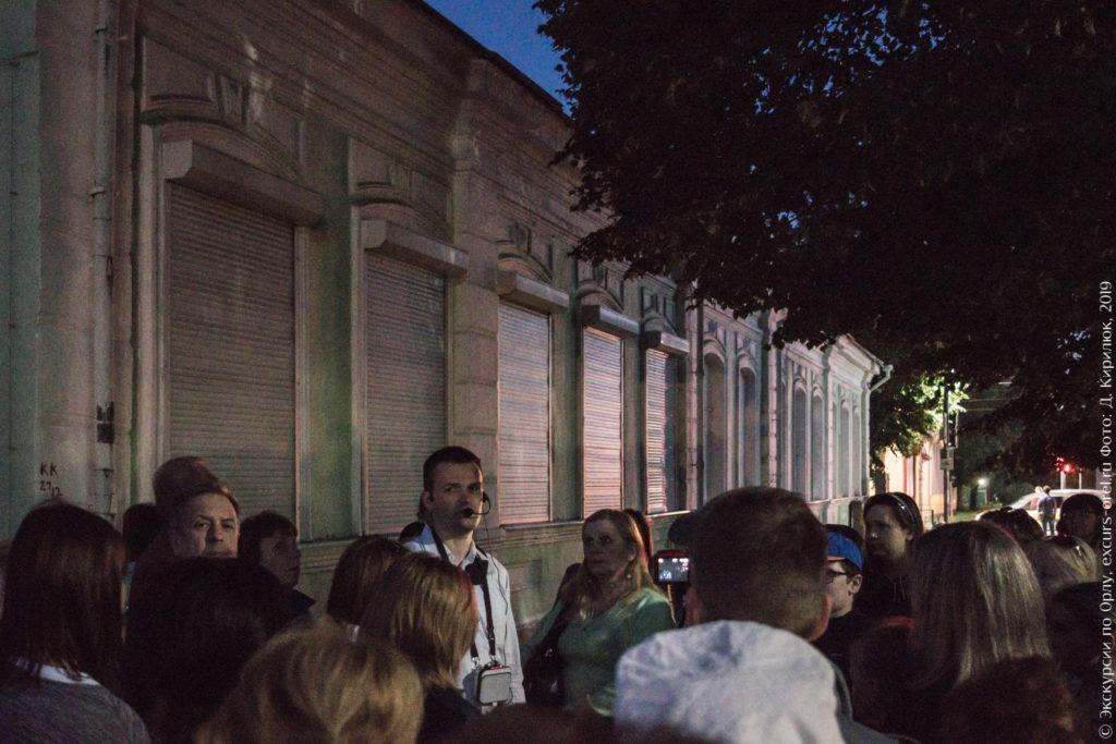 Экскурсанты перед вытянутым одноэтажным каменным зданием с высокими окнами и светло-зелеными стенами, сумерки.