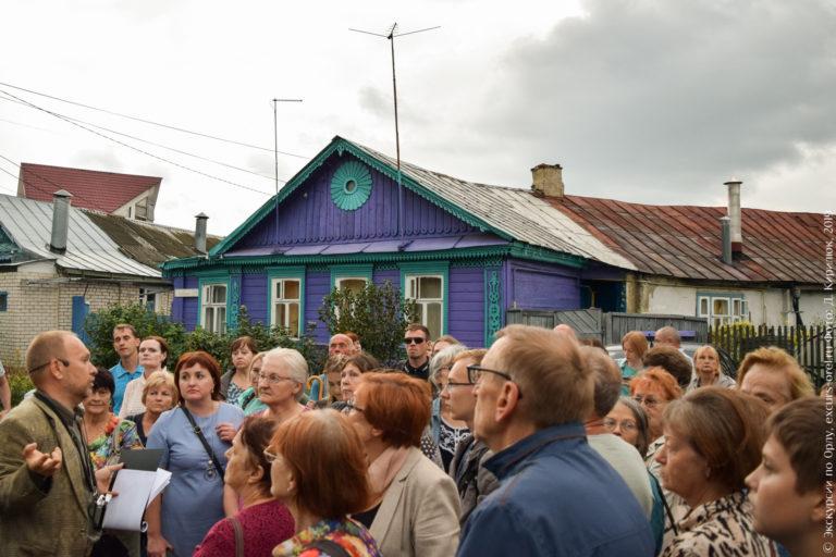 Экскурсанты на фоне как бы скругленного дома, фасад украшен резьбой и покрашен в фиолетовый и зеленый цвета.