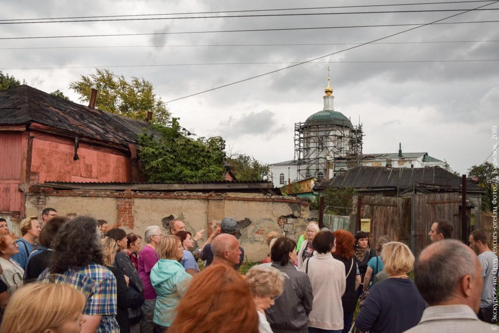 Однокупольная большая церковь без колокольни за неприглядным забором и постройками.