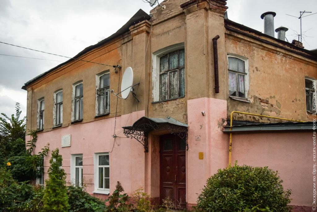 Двухэтажный обшарпанный каменный дом с кованым козырьком и мемориальной доской.