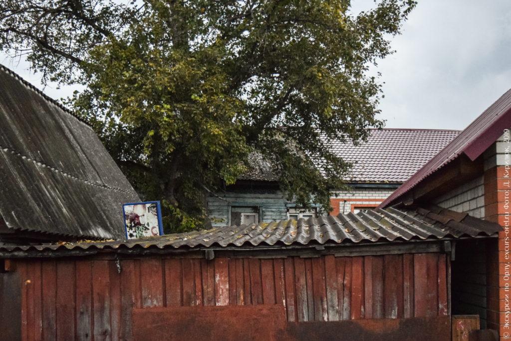 Часть одноэтажного дома выглядывает из-за забора и построек.
