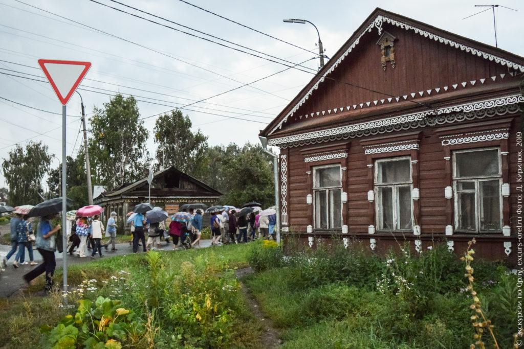 Деревянный дом коричневого цвета, богато украшенный белой резьбой. Через дорогу от него обгорелый дом, тоже с резьбой на фасаде. И экскурсанты идут под зонтами.