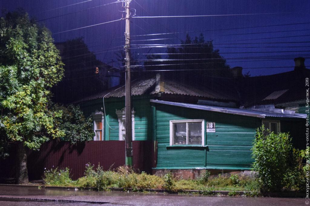Деревянный зеленый дом с белыми наличниками, основной фасад под углом к улице.
