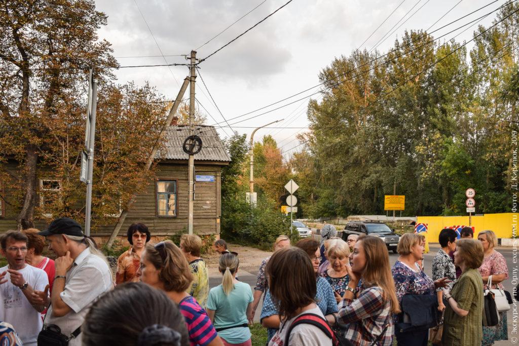 Люди на фоне деревянного дома ремонтируемого моста, перекрытого желтым забором. За мостом - высокие деревья.