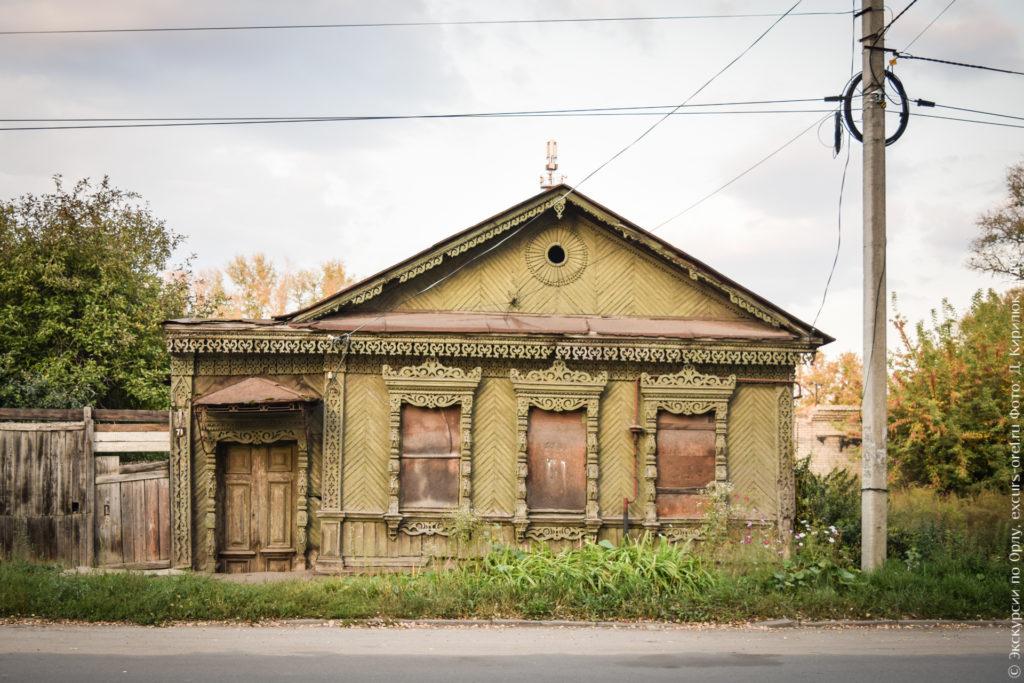 Одноэтажный деревянный дом в три окна с пристроенной верандой, окна закрыты фанерой. Дом светло-зеленого цвета.