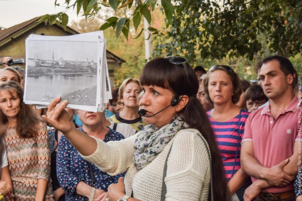 Экскурсовод показывает старый вид города со стороны реки, видны три церкви.