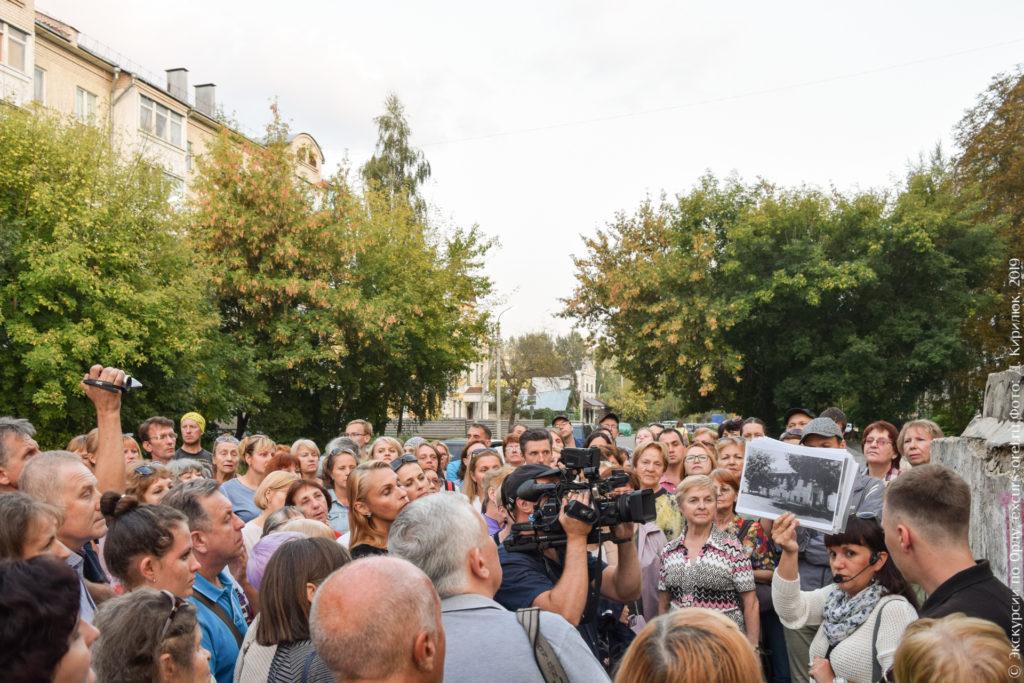 Экскурсанты на фоне деревьев и новостроек, экскурсовод показывает фото дома, которого больше нет.